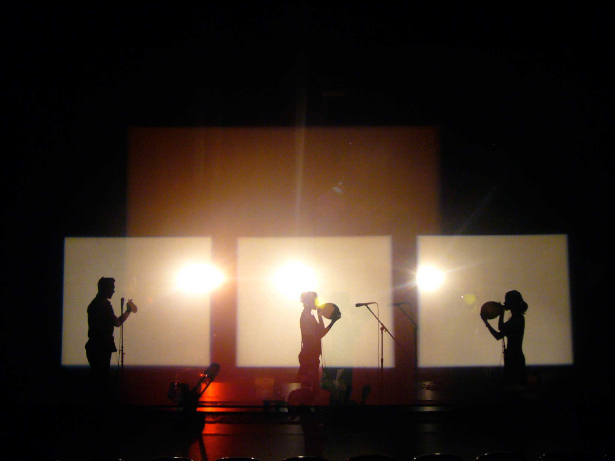 Three performers blowing up balloons,, silhouetted in separate rectangles of stage light (Whisper).