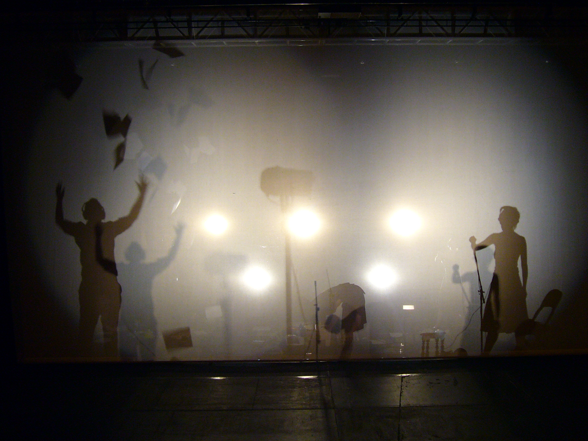 Three performers in silhouette against a gauze screen. One of them is throwing armfuls of paper in the air. (Whisper).