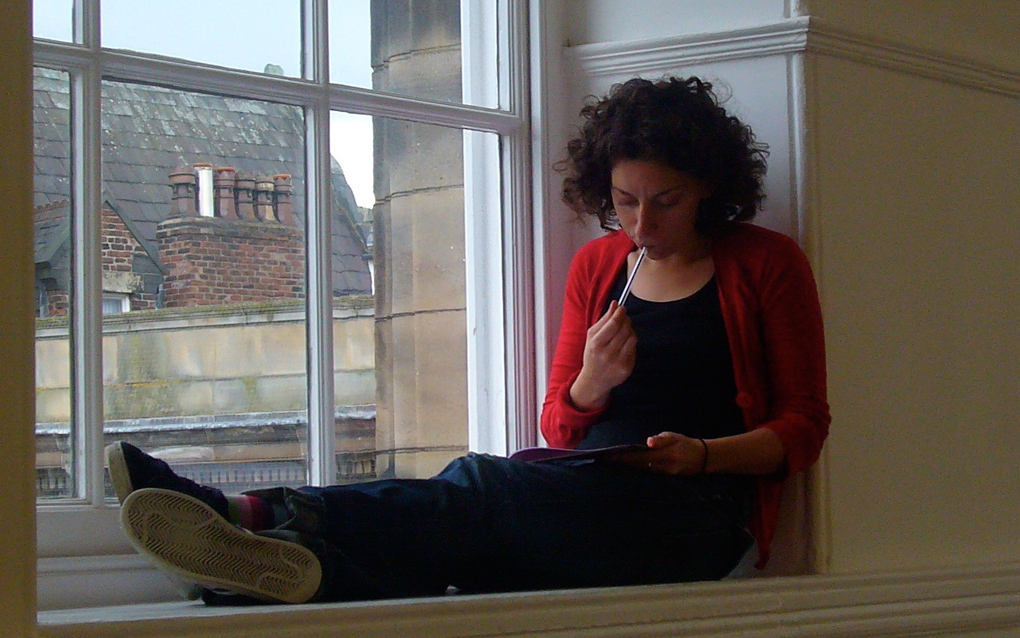 A Proto-type Summer School participant sits on a wide window ledge holding a pen to their mouth, and stares down at a notebook.
