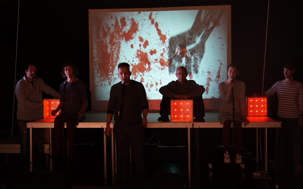 3 performers with microphones, and 3 musicans with cubes full of red light, sit on the edge of the stage. A drawing of a bloody fist is projected behind them. (the Good, the God, and the Guillotine).