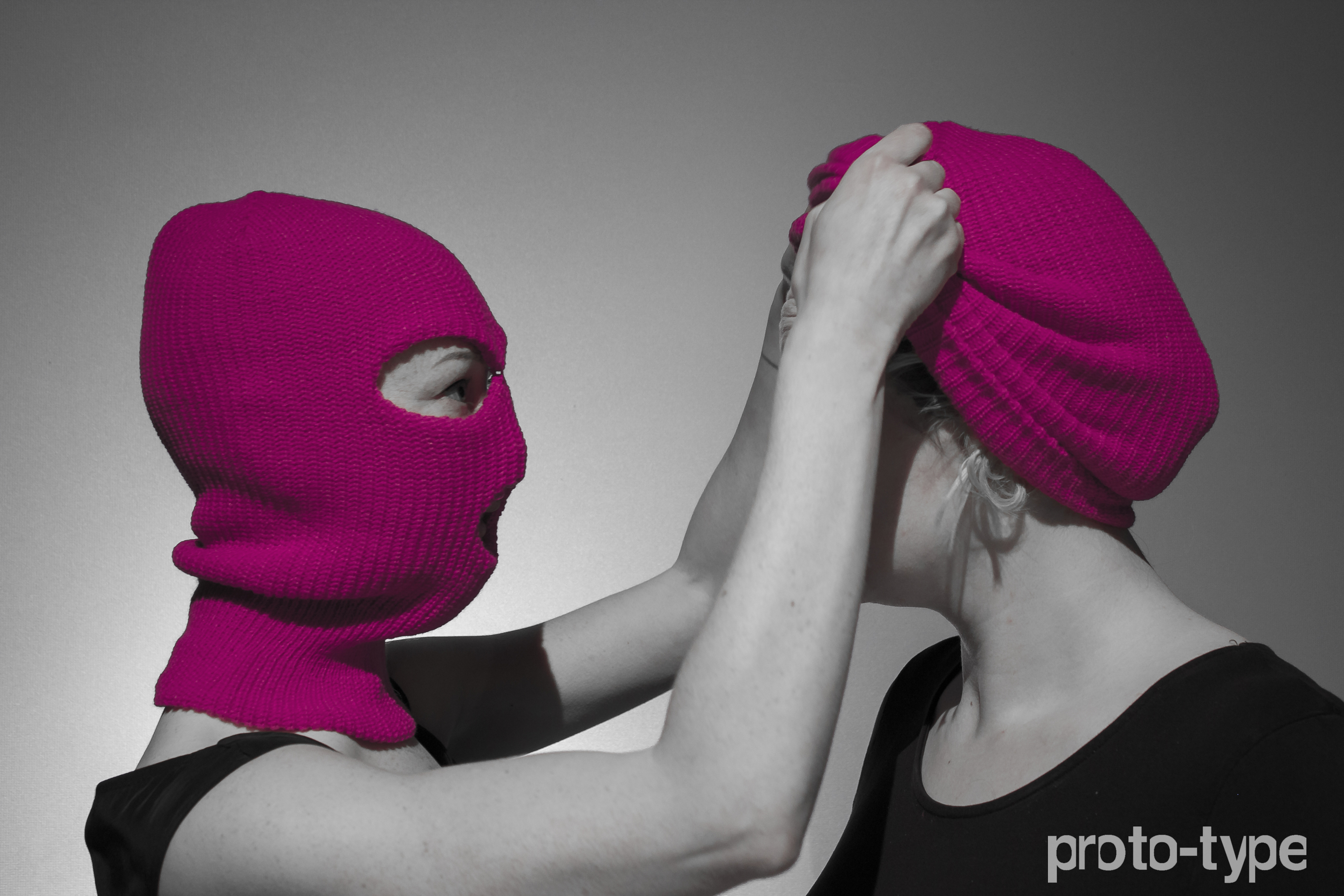 Main promo image for Proto-type Theater's 'A Machine they're Secretly Building'. Two women wearing hot pink balaclavas facing each other. It's not clear whether the balaclavas are being put on or taken off.