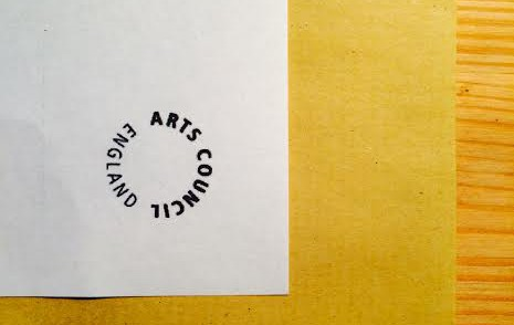 An 'Arts Council Enland' logo, ink- tamped onto the corner of an envelope.