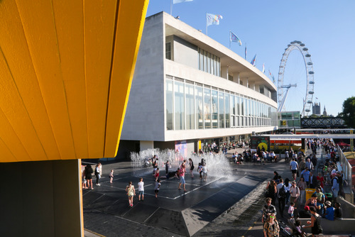 An exterior view of the Southbank Centre with the London eye in the distance.