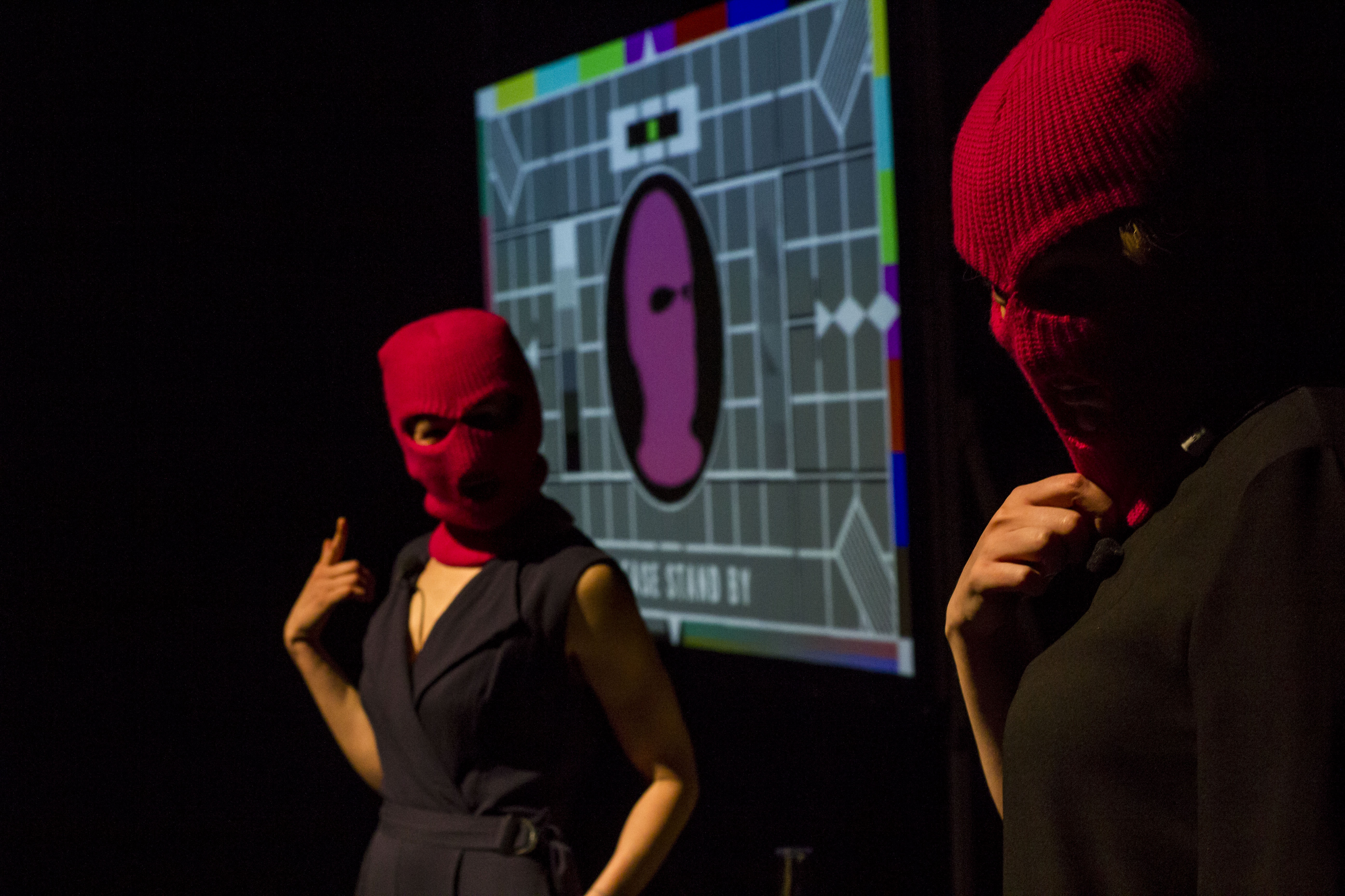 "Two figures in pink balaclavas stand before a 'Test Card' style image with the words ""Please stand by..."""
